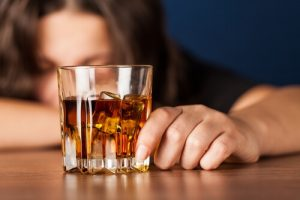 drunk woman with glass full of whiskey lying on a bar rack