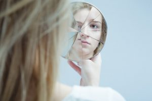 depressed woman looking into the broken mirror