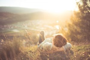 carefree woman lying on the grass watching the sunset