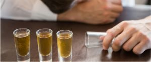 drunk man holding an empty glass with whiskey shots on table