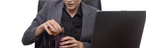 woman secretly pouring alcohol into her coffee cup at her workplace