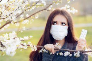 woman with allergy holding antihistamine pills
