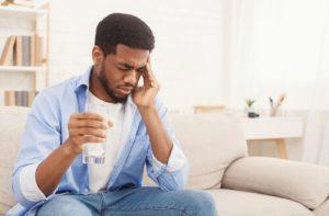 man with hangover headache takimg pills
