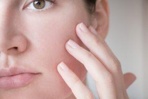 woman touching her facial skin