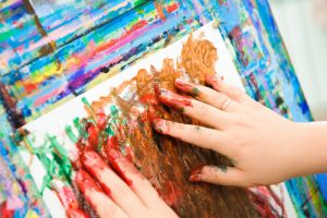 woman painting with fingers on art therapy session