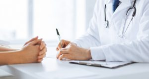 doctor making notes at the consultation with the patient