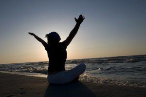 woman meditating on beach